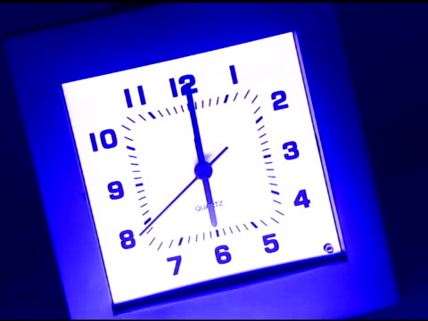undercranked tilt down to a square clock at 6:00. - tungsten image stock videos and b-roll footage