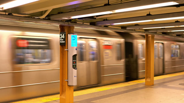 underground in the transportation hub. 34th street, penn station subway. train coming to platform. new york, us - 自動改札機点の映像素材/bロール