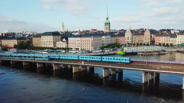 stockvideo's en b-roll-footage met ondergrondse treinverkeer crossing bridge, stockholm city silhouette - stadsdeel
