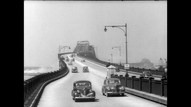 / underneath the pulaski skyway looking at construction details / cars driving towards camera across bridge pulaski skyway on january 01 1946 in... - 1946年点の映像素材/bロール