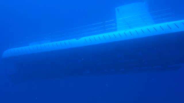underwater: a submarine moving slowly through bright blue water - sottomarino subacqueo video stock e b–roll