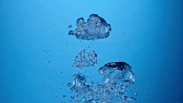 SLO MO Underwater air pockets on blue background