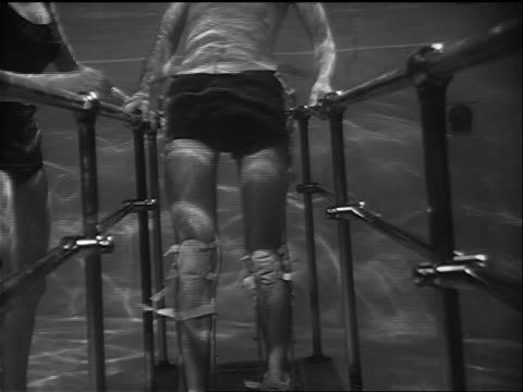 B/W 1958 underwater disabled man's legs in braces walking in pool / man holds onto bars