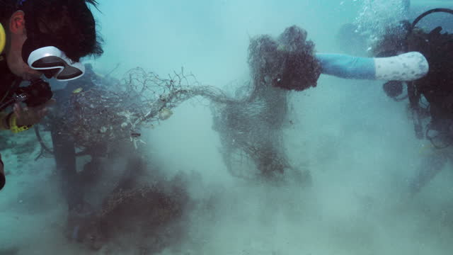 underwater environmentalist scuba divers removing tangled fishing net - aqualung diving equipment stock videos & royalty-free footage