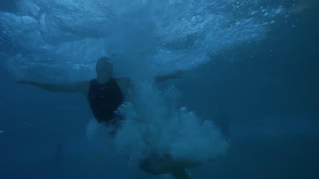 vídeos y material grabado en eventos de stock de underwater footage of female swimmer diving into the pool - traje de baño de una pieza