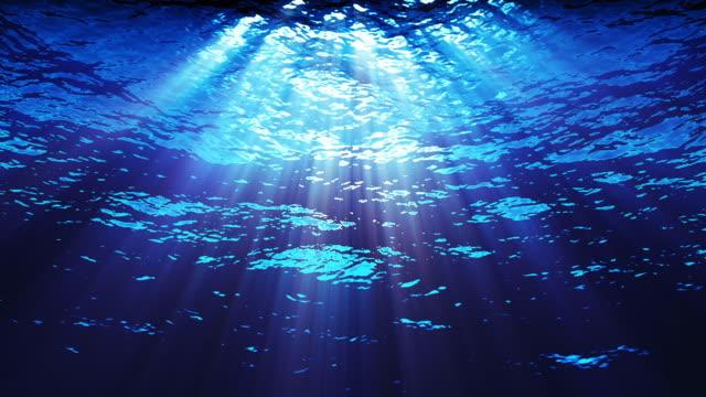 Underwater light filters down through blue water.