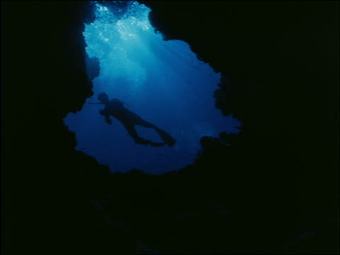 underwater low angle scuba diver swims past hole
