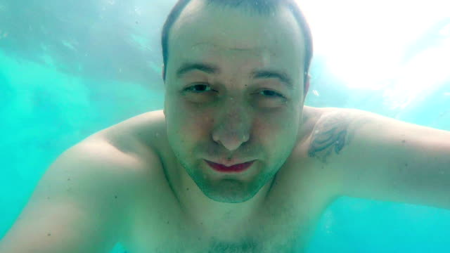 Underwater man portrait in swimming pool.