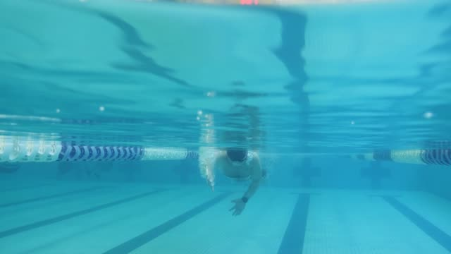 underwater: man swimming past camera - swimming stock videos & royalty-free footage
