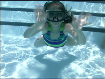stockvideo's en b-roll-footage met underwater medium shot of girl swimming and waving to viewer. - swimwear