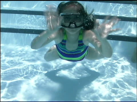 underwater medium shot of girl swimming and waving to viewer. - swimwear stock videos & royalty-free footage