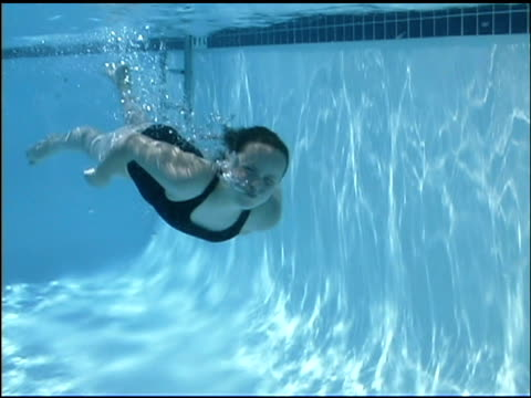underwater medium shot of girl swimming past the viewer. - swimming costume stock videos and b-roll footage