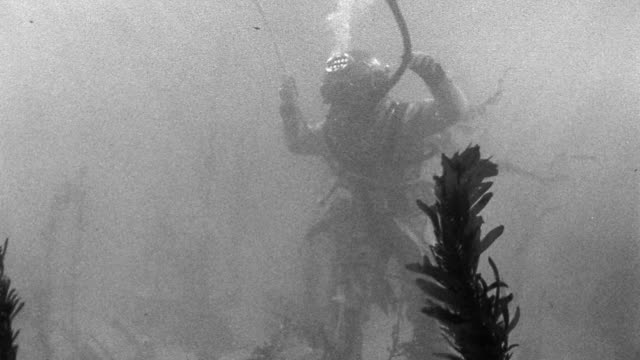 b/w underwater person wearing early diving suit with rope tied around waist walking on ocean floor - helmet stock videos & royalty-free footage
