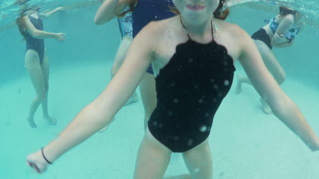 Underwater portrait of girl waving at camera in swimming pool / Cedar Hills, Utah, United States