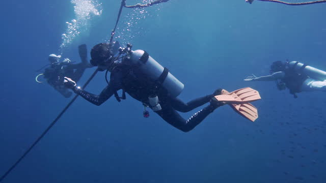 underwater scuba divers communicating navigation using hand signals - aqualung diving equipment stock videos & royalty-free footage