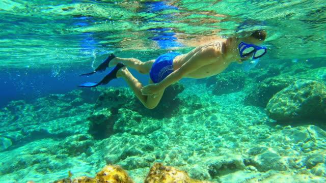 stockvideo's en b-roll-footage met onderwater schot: jongen snorkelen in het ondiepe water observeren van het onderwaterleven - middellandse zee
