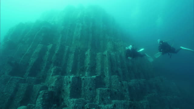 Underwater shot; Divers swimming near the underwater columnar joints off the coast of the Shakotan Peninsula, Hokkaido, Japan.
