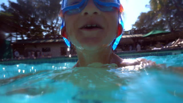 underwater shot of a boy playing in a pool at a hotel resort. - slow motion - mouth open stock videos & royalty-free footage