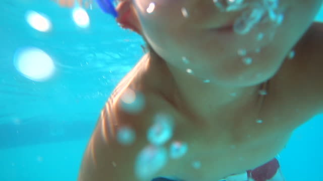 underwater shot of a boy playing in a pool at a hotel resort. - slow motion - nackter oberkörper stock-videos und b-roll-filmmaterial