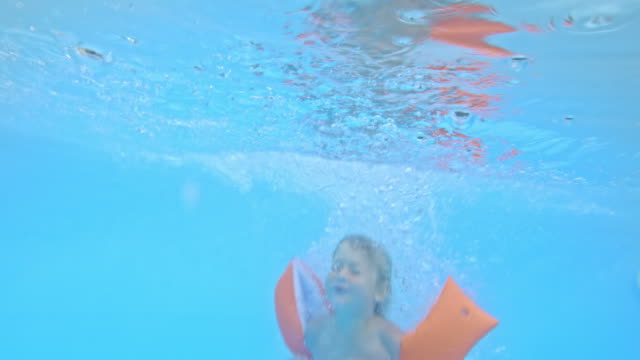 TD Underwater shot of a boy with swimmies jumping into the pool