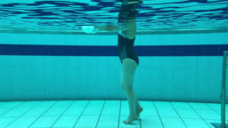 Underwater shot of a woman doing hydrotherapy exercises using free weights