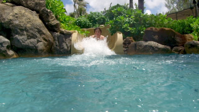 Underwater shot of boy coming down pool slide