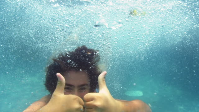 Underwater shot of boy in a pool giving two thumbs up to camera