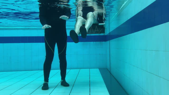 underwater shot of therapist instructing patient how to exercise his legs during hydrotherapy - hydrotherapy stock videos & royalty-free footage