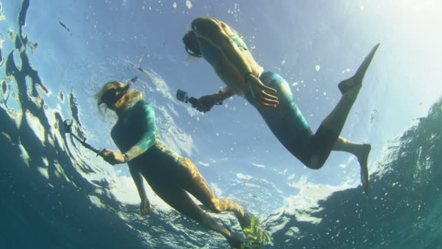 Underwater shot of two girls looking around while they snorkel in the deep ocean