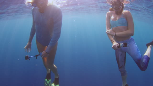 underwater shot of two girls on the surface looking down at the abiss below them - タートル湾点の映像素材/bロール