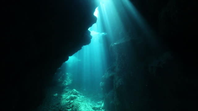 Underwater shot of underwater cave showing shower of light reaching the seafloor