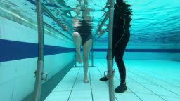 Underwater shot of woman walking with the help of parallel bars next to her physiotherapist