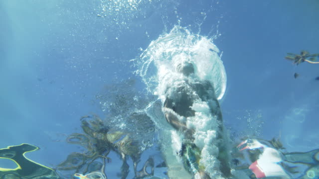 underwater shot of young boy jumping in a swimming pool - winken stock-videos und b-roll-filmmaterial