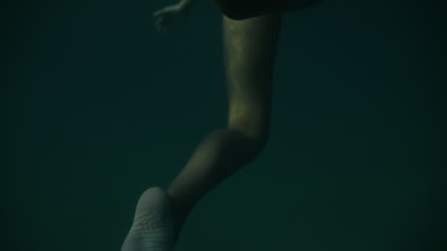 underwater shot of young woman swimming in sea - under her feet stock videos & royalty-free footage
