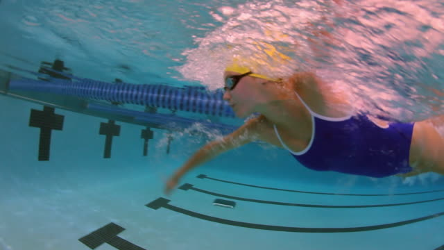 underwater side view of a female professional swimmer racing freestyle and turning around at the end of the swimming lane during a swim meet in an indoor olympic sized swimming pool - 耐久力点の映像素材/bロール