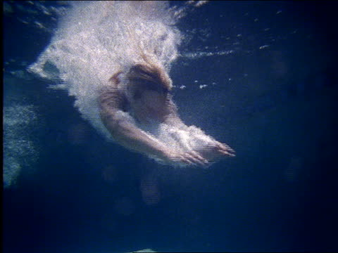 vídeos de stock e filmes b-roll de underwater slow motion woman diving into swimming pool - mergulhar para a água