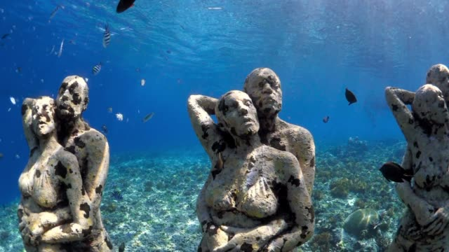 vídeos de stock e filmes b-roll de underwater statues of couples hugging, in tropical water with fish - estátua