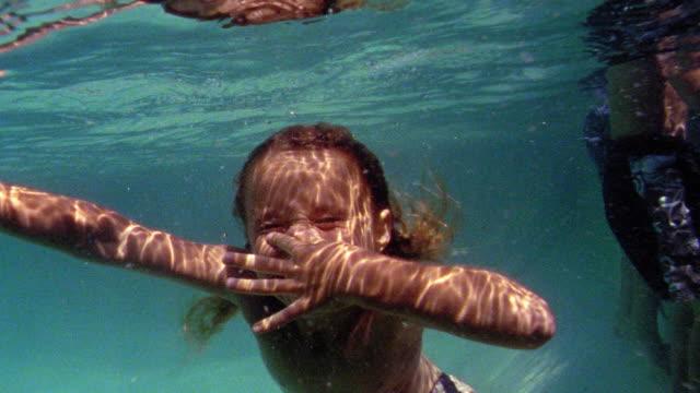 vídeos de stock, filmes e b-roll de underwater swimming point of view toward girl holding nose with eyes closed underwater - prendendo a respiração