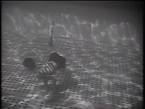 b/w 1934 underwater tilt up swimming boy grabbing plates from bottom of swimming pool / cruise ship - 1934 stock videos & royalty-free footage