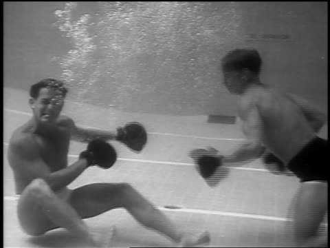 B/W 1939 underwater two men with boxing gloves punching each other / one victorious / Palm Springs, CA