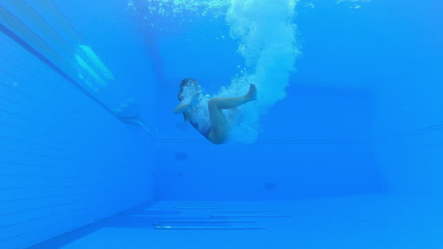 slo mo ld underwater view of a female diver landing in the pool in a cloud of bubbles - swimwear stock videos & royalty-free footage
