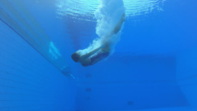 LD Underwater view of a female diving athlete landing in the pool and turning in a cloud of bubbles
