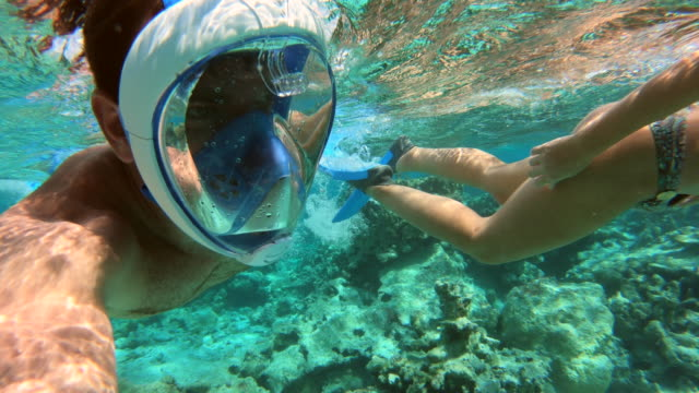 Underwater POV view of a man and woman couple snorkeling swimming around scenic tropical islands.