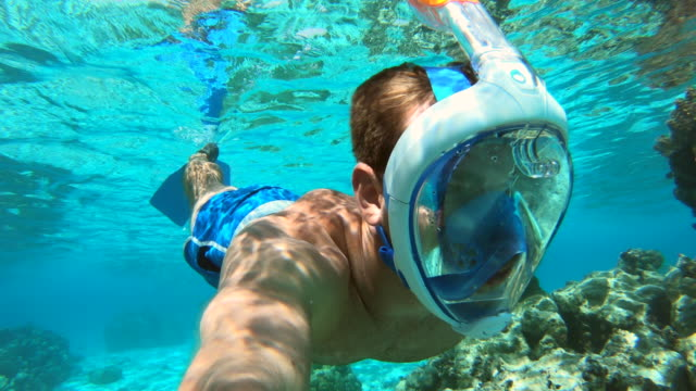 underwater pov view of a man and woman couple snorkeling swimming around scenic tropical islands. - south pacific ocean stock videos and b-roll footage