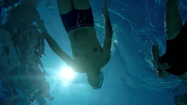 Onderwater weergave van een jong koppel zwemmen in het zwembad