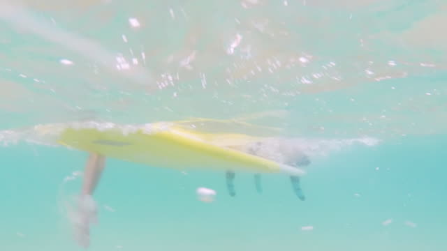 Underwater view of female surfer paddling on yellow surfboard in clear water in ocean in bikini in Southern France
