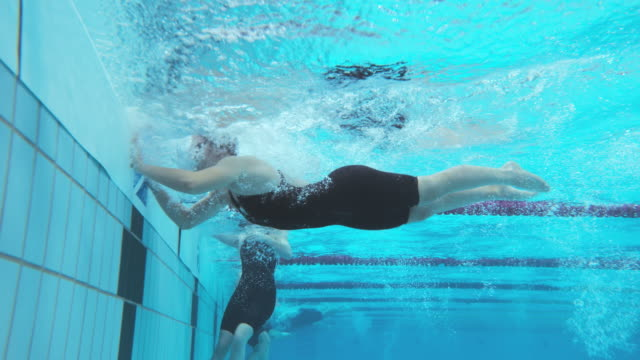 Underwater view of female swimmers finishing the competition in butterfly style