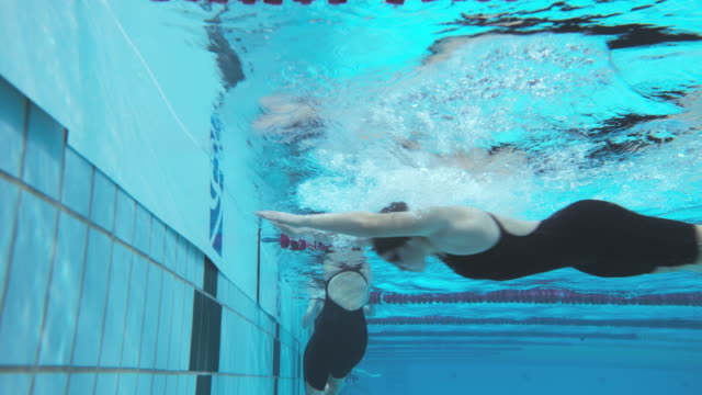 Underwater view of female swimmers reaching the finish