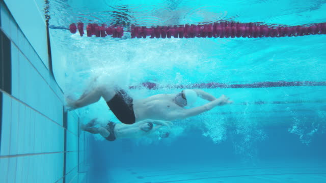 underwater view of male swimmers doing flip turn in competition - swimming stock videos & royalty-free footage