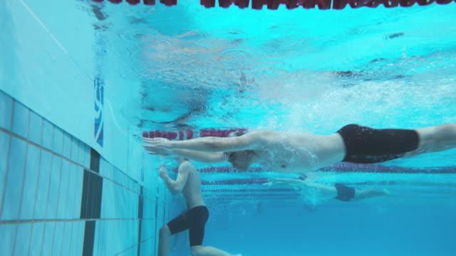 vídeos de stock, filmes e b-roll de underwater view of male swimmers reaching the finish - touca de natação
